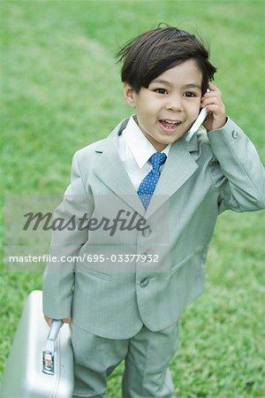 Jeune garçon habillé en costume, à l'aide de téléphone portable, mallette de transport