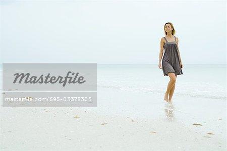 Femme en robe bain de soleil à pied à la plage, à la recherche de suite