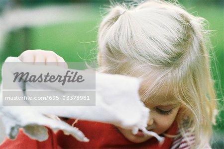 Kleines Mädchen hält Küchentuch, Blick nach unten, Nahaufnahme