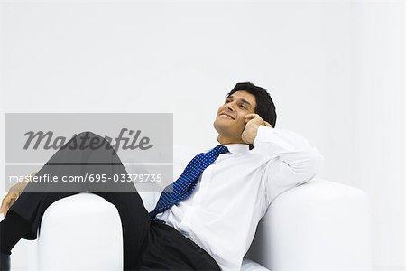 Mann im Sessel, Leiter Betrieb, liegend lächelnd