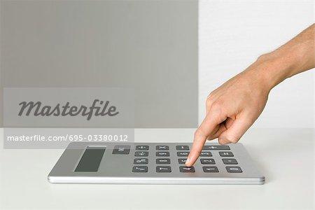 Hand using oversized calculator