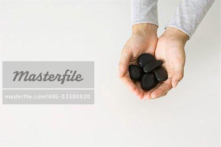 Hands holding black stones, overhead view