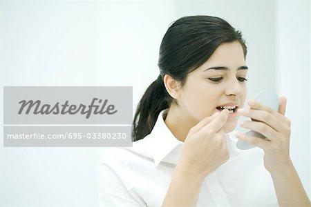 Jeune femme elle-même en regardant dans le miroir de poche pour prendre quelque chose hors de ses dents