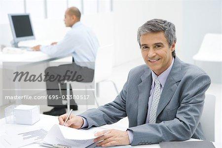 Geschäftsmann, arbeiten am Schreibtisch, in die Kamera lächelnd, Kollege im Hintergrund