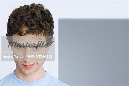 Homme ricaner à la caméra, un sourcil soulevé