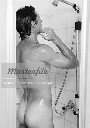 Man taking shower, rear view, b&w