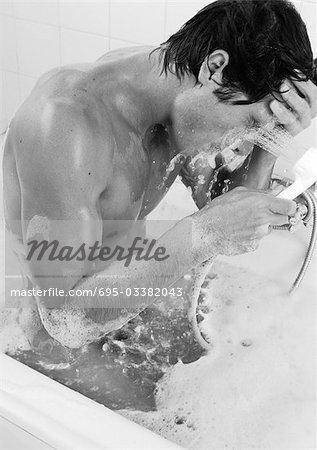 Homme prenant bain aux bulles, lavage de visage, gros plan, b&w