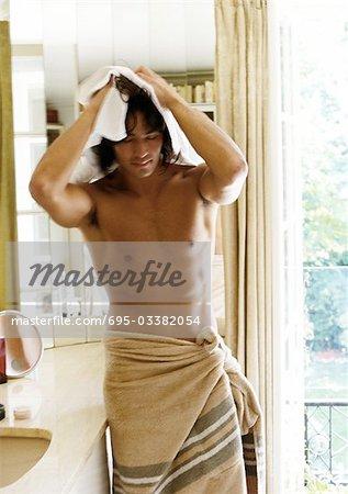 Homme avec une serviette enroulée autour debout de taille dans les cheveux sécher à la serviette de bain