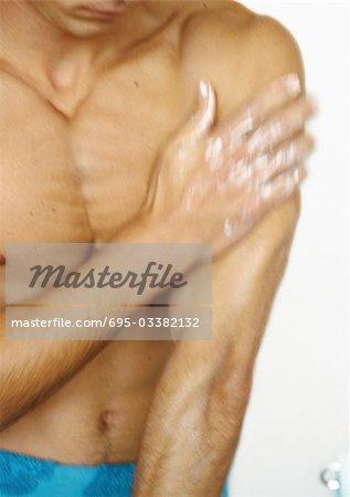 Homme torse nu avec la main sur le bras, se concentrer sur le torse, flou