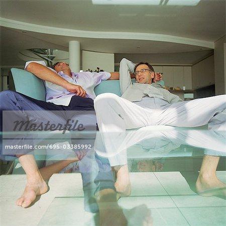 Zwei Männer mit Beinen setzte sich auf dem Sofa sitzen