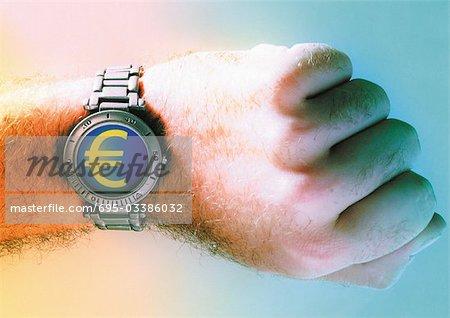 Euro sign on man's wrist watch.