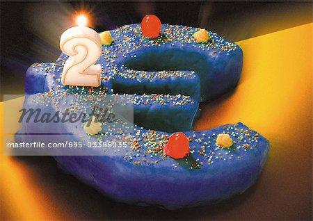 Gâteau d'anniversaire signe euro, numéro bougie deux brûler sur le dessus.