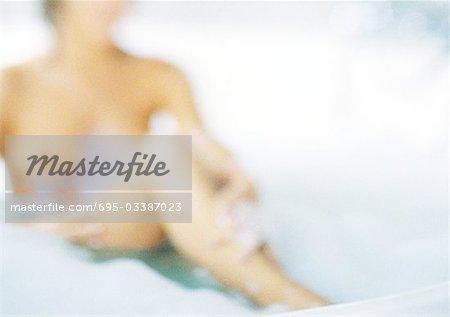 Femme dans un bain moussant, floue.