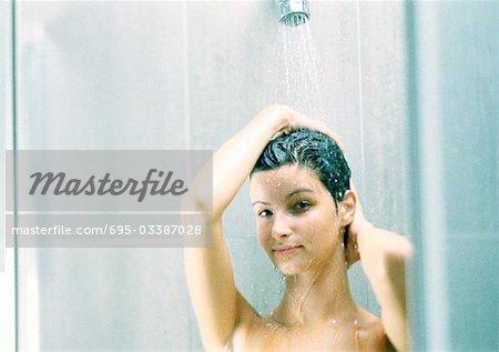 Woman taking shower, looking at camera, close-up.