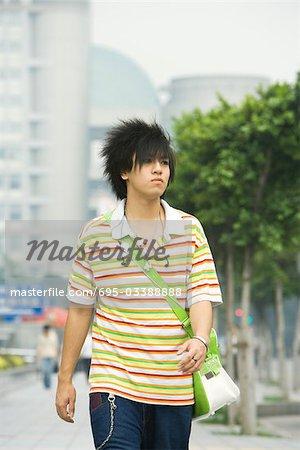 Teenage boy walking in urban setting