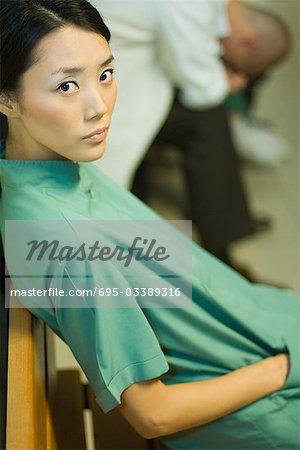 Medizinische ArbeiterIn mit Hand in der Tasche sitzen, Blick in die Kamera, Arzt mit Kopf nach unten im Hintergrund