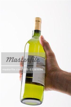 Hand holding up bottle of white wine