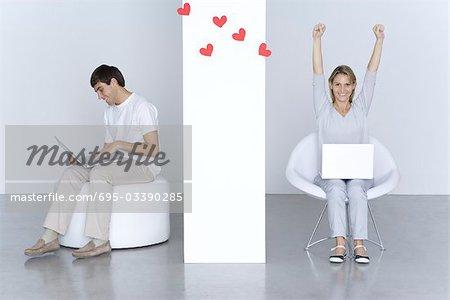 Homme et femme à l'aide d'ordinateurs portables, coeurs flottants entre eux, a soulevé des bras de la femme