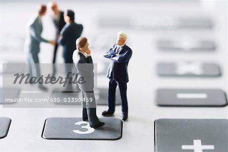 Miniature businessmen negotiating on calculator