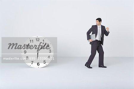 Homme d'affaires muni document, regarder par-dessus l'épaule, étonné de l'horloge