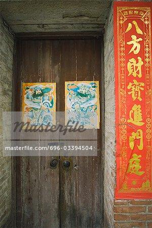 Chine, porte d'entrée avec affiches, bannières avec des caractères chinois à côté de la porte