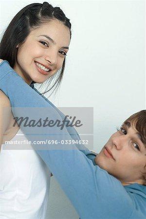 Jeune couple, l'homme atteignant jusqu'à mettre bras autour de cou de la femme, portrait