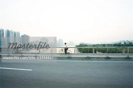Chine, Province du Guangdong, Guangzhou, cyclistes traversant le pont, gratte-ciels à distance
