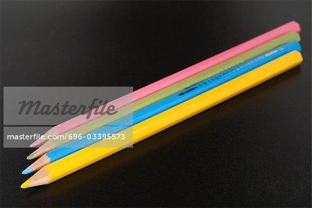 Quatre crayons de couleur côte à côte, gros plan