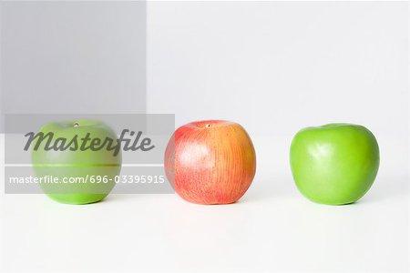 Trois pommes dans une rangée, deux vert et un rouge en gros plan