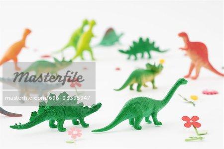 Dinosaures en plastique entourés de fausses fleurs