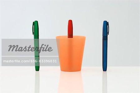 Stylos debout dans une ligne, la plume moyenne à l'envers à l'intérieur de la tasse