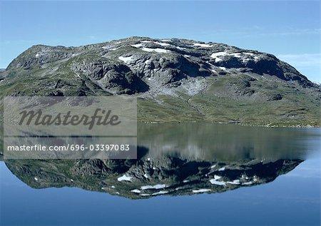 Norvège, moussue, terrain rocheux patché à la neige reflète dans la mer