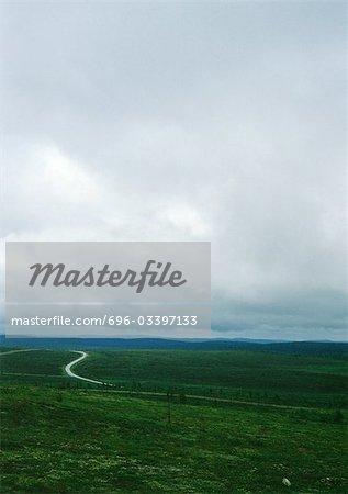 Iceland, road through plain under cloudy sky