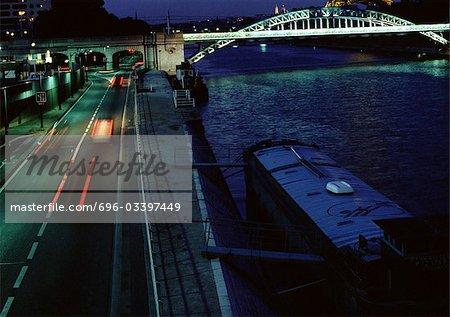 France, Paris, cars traveling on quai at night, blurry.