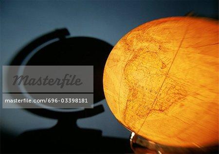 Illuminated globe and shadow on wall