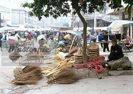 Chine, région autonome du Guangxi Laibin, vendeur de balai au marché en plein air
