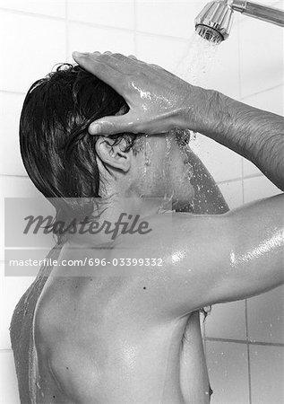 Man taking shower, side view, b&w