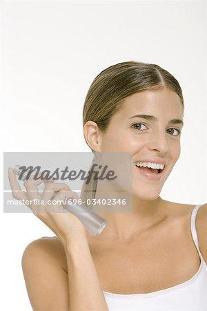Femme tenant la bouteille de parfum, souriant à la caméra