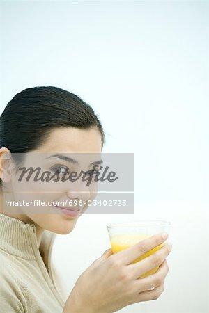 Jeune femme tenant le verre de jus d'orange, souriant à la caméra