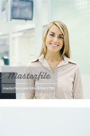 Femme debout derrière le comptoir, souriant à la caméra, portrait