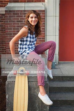 Frau sitzt auf der Treppe mit Skateboard, Portland, Oregon, USA