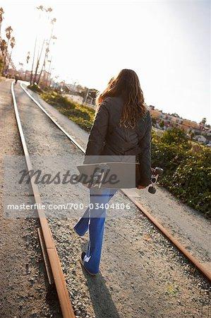 Junge Frau hält Skateboard
