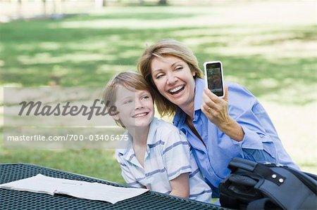 Mutter und Sohn sitzen im Park mit Handy, ein Bild des selbst zu übernehmen