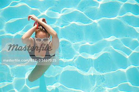 Vue surélevée d'une femme debout dans une piscine avec bras croisés par-dessus la tête
