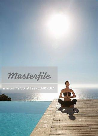 Jeune femme à pratiquer l'yoga, une piscine avec l'océan en arrière-plan