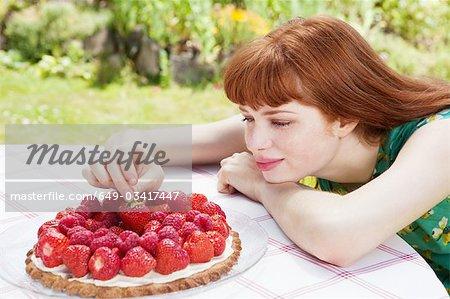 jeune femme cueillette de fraises de tarte.