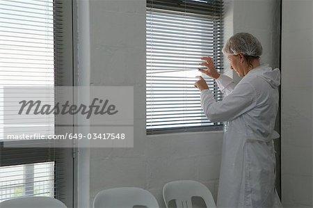 Ouvrier d'usine lorgnant à travers les aveugles