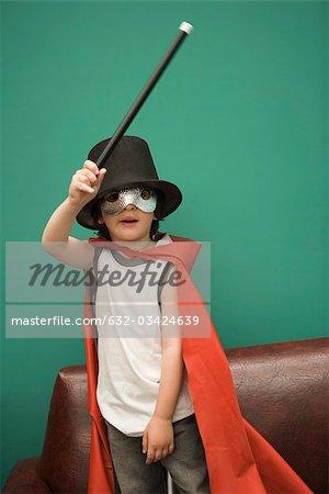 Garçon en costume prétendant être magicien