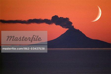 USA, Alaska. Un croissant de lune s'élève au-dessus de Mont Augustine durant une phase éruptive en 1986. Mont Augustine est le long de la péninsule de l'Alaska dans Cook Inlet environ 70 km SW d'Homère.