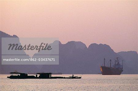Bateaux à Ha Long Bay au coucher du soleil. Ha Long Bay s'étend plus de 1500 kilomètres carrés de la golfe du Tonkin, au coin nord-est du Vietnam, avec plus de 3000 îles dans ses eaux. Ha Long Bay a été déclaré site du patrimoine mondial par l'UNESCO.